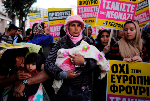 A woman holds a baby in her arms as she takes part in a demonstration by Greek anti-fascist groups against the war in Syria and the European Union's stance on refugees Photo: Milos Bicanski/Getty Images