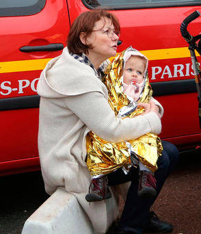 A woman holds her baby outside Orly airport after a gunman forced evacuation of the terminal south of Paris Photo: AP Photo/Thibault Camus