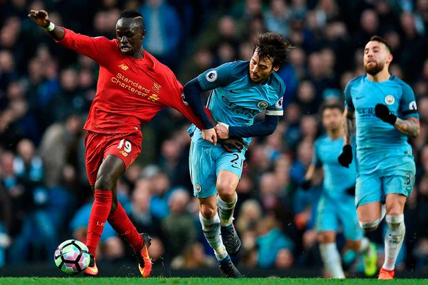Liverpool's Senegalese midfielder Sadio Mane (L) is held back by Manchester City's Spanish midfielder David Silva. Photo: Getty Images