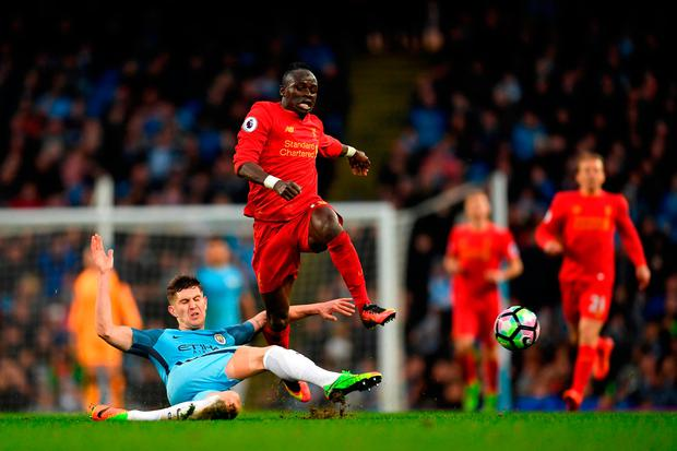 John Stones of Manchester City (L) tackles Sadio Mane of Liverpool (R). Photo by Laurence Griffiths/Getty Images