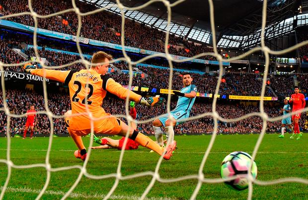 Sergio Aguero of Manchester City (R) scores his sides first goal past Simon Mignolet of Liverpool. Photo by Michael Regan/Getty Images