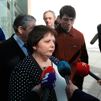 Angela Murray is surrounded by family as she speaks about the death of her husband John Photo: Collins