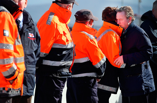 Taoiseach Enda Kenny hugs a member of the Civil Defence alongside members of the Coast Guard during a visit to Blacksod in Co Mayo. Photo: Steve Humphreys