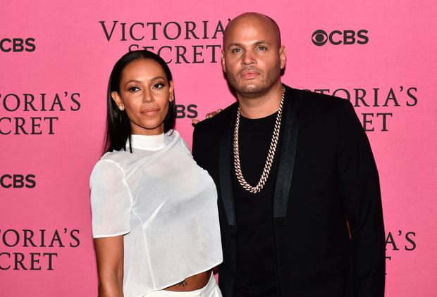 British singer Melanie Brown and her husband Stephen Belafonte poses for pictures on the pink carpet with an unidentified guest upon arrival for the 2014 Victoria's Secret Fashion Show at Earl's Court exhibition centre in London