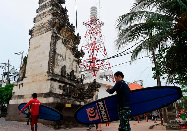foreign tourists past in front a tower warning of tsunami in kuta near denpasar on