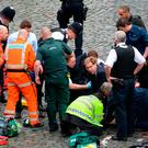 Conservative MP Tobias Ellwood (centre) helps emergency services attend to a police officer outside the Palace of Westminster, London, after a policeman was stabbed and his apparent attacker shot by officers in a major security incident at the Houses of Parliament. Photo: Stefan Rousseau/PA Wire