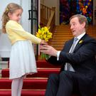 Millie Sunderland (6), from Ringsend in Dublin, presents a bunch of daffodils to Taoiseach Enda Kenny ahead of Daffodil Day tomorrow. Photo: Tony Gavin
