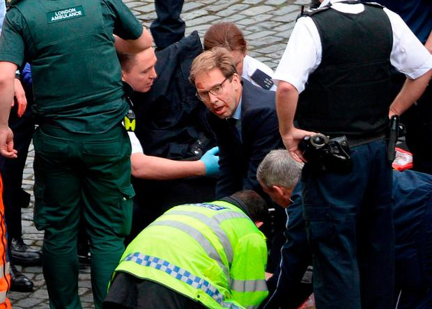 British Minister Tobias Ellwood is pictured helping the injured police officer. Photo: PA