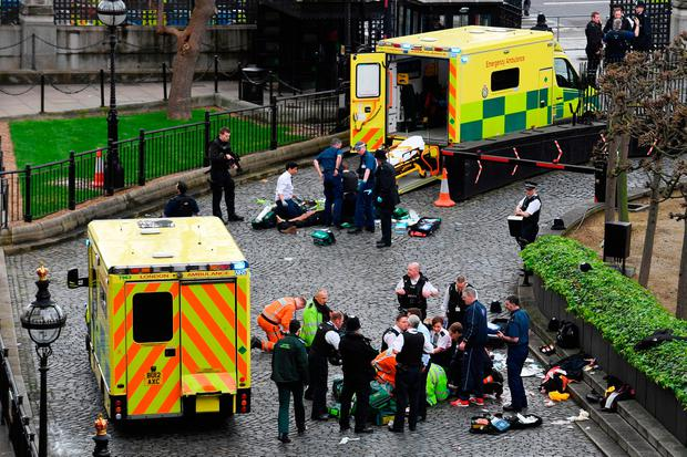 Emergency services attend the attacker, top, and a police officer, bottom, outside the Palace of Westminster. Photo: PA Wire