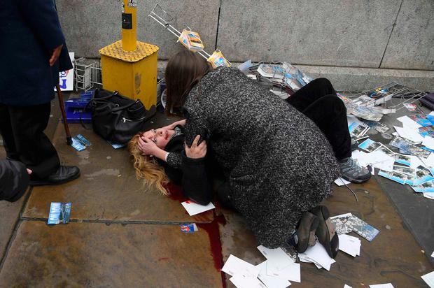 A heavily bleeding woman is helped at the scene. Photo: REUTERS