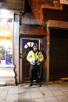 A police officer stand outside an address in Hagley Road, Birmingham, where armed police have raided a flat overnight. West Midlands Police have directed media queries to the Met Police, who have refused to discuss the incident for operational reasons. Photo: Richard Vernalls/PA Wire
