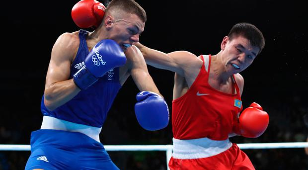 Abialkhan Zhussupov of Kazikstan (red) fights Pat McCormack of Britain (blue) in Rio