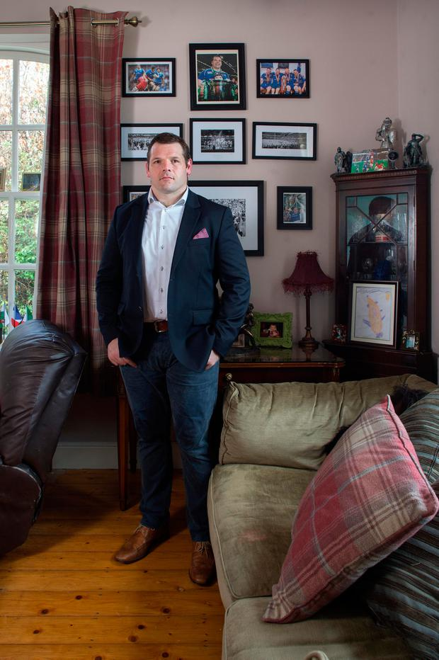 Mementos: Mike in front of some rugby memorabilia in the living room. Photo: Tony Gavin