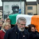 Sinn Feinn President Gerry Adams (C) walks alongside the coffin of Martin McGuinness as it is carried through crowded streets during his funeral in Londonderry, Northern Ireland. REUTERS/Clodagh Kilcoyne