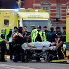 Emergency services transport an injured person to an ambulance, close to the Houses of Parliament in London, Wednesday (AP Photo/Matt Dunham)