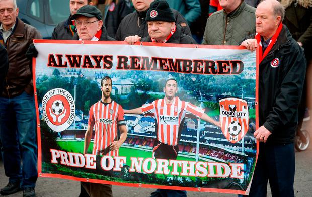 Derry City supporters pay tribute to two of their fallen heroes during Ryan McBride's funeral. Photo: Oliver McVeigh / Sportsfile