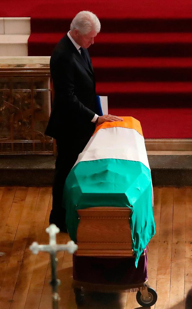 Former US president Bill Clinton pauses to touch the coffin after speaking at the funeral of Martin McGuinness in Derry. Photo: Niall Carson/PA