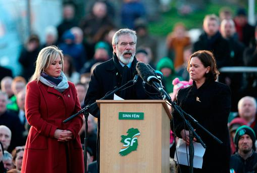 Sinn Fein's Michelle O'Neill, Gerry Adams and Mary Lou McDonald speak at Derry City Cemetery after the funeral service of Martin McGuinness. Photo: PA