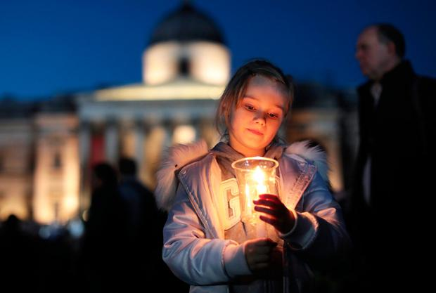A young girl lights a candle during a candlelit vigil at Trafalgar Square. Photo: GETTY
