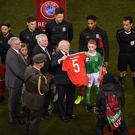 Dublin , Ireland - 24 March 2017; President of Ireland Michael D. Higgins holds a jersey, displaying the name and number of the late Derry captain Ryan McBride, given to him by Ashley Williams of Wales ahead of the FIFA World Cup Qualifier Group D match between Republic of Ireland and Wales at the Aviva Stadium in Dublin. (Photo By Stephen McCarthy/Sportsfile via Getty Images)