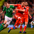 James McClean battles for possession with Chris Gunter in the Aviva Stadium. Photo: Sportsfile