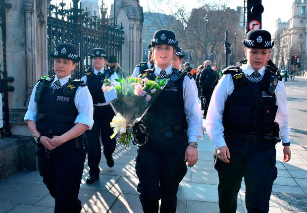 Police leave flowers outside parliament in London in tribute to the victims of Khalid Masood Picture: PA