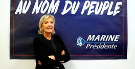 France's far-right National Front leader Marine Le Pen poses in front of a poster for her 2017 French presidential election campaign (REUTERS/Charles Platiau)