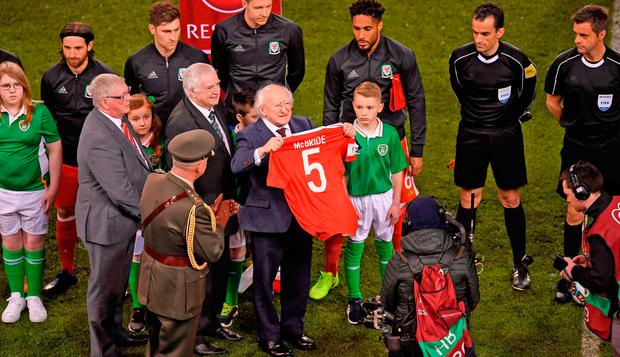 President Michael D Higgins holds a jersey displaying the name and number of the late Ryan McBride, given to him by Wales captain Ashley Williams. Photo: Sportsfile