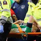 Republic of Ireland's defender Seamus Coleman is taken from the pitch on a stretcher after being injured during the World Cup 2018 qualification football match between Republic of Ireland and Wales at Aviva Stadium in Dublin, Ireland on March 24, 2017. The game ended 0-0. / AFP PHOTO / Paul FAITH