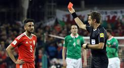 Wales' defender Neil Taylor (L) is shown a red card by Italian referee Nicola Rizzoli for a horror tackle on Seamus Coleman back in March
