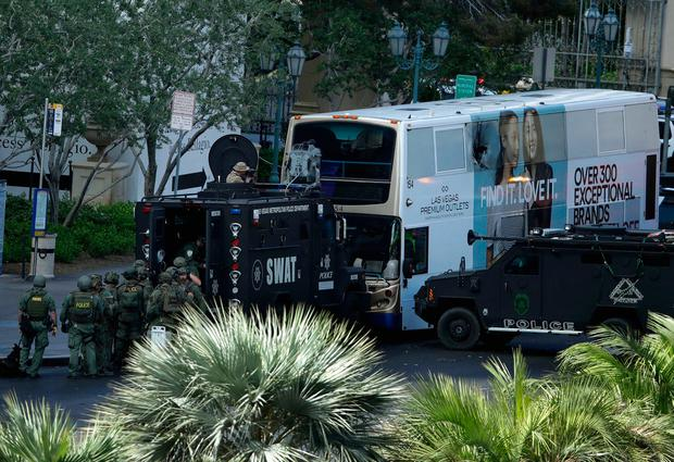 Las Vegas SWAT officers surround a bus along Las Vegas Boulevard, Saturday, March 25, 2017, in Las Vegas. Police say part of the Strip has been closed down after a shooting. (AP Photo/John Locher)