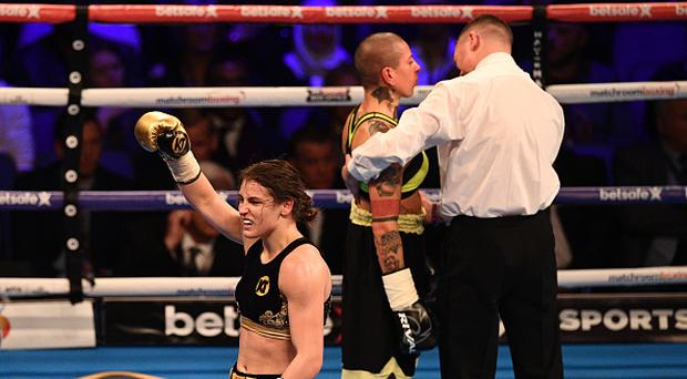 Irish boxer Katie Taylor (L) celebrates beating Italian boxer Monica Gentili (C) after their super featherweight boxing match at the O2 Arena in London on March 4, 2017. Taylor won with a fifth-round stoppage of Gentili. / AFP PHOTO / Justin TALLIS (Photo credit should read JUSTIN TALLIS/AFP/Getty Images)