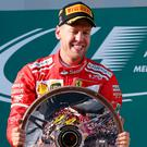 Ferrari's Sebastian Vettel celebrates after being presented with the trophy following his victory in the Australian Grand Prix in Melbourne. Image: AP Photo/Rick Rycroft