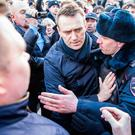 Russia's leading opposition figure Alexei Navalny is detained by police in downtown Moscow during a mass protest. Photo: AP