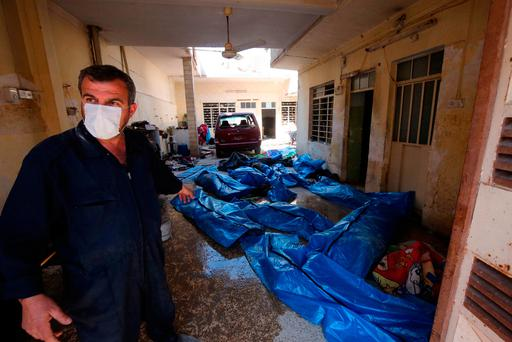 An Iraqi rescue worker gestures towards bodies wrapped in plastic in Mosul's al-Jadida area following air strikes in which civilians have been reportedly killed during an ongoing offensive against the Islamic State group. Photo: AFP/GETTY IMAGES