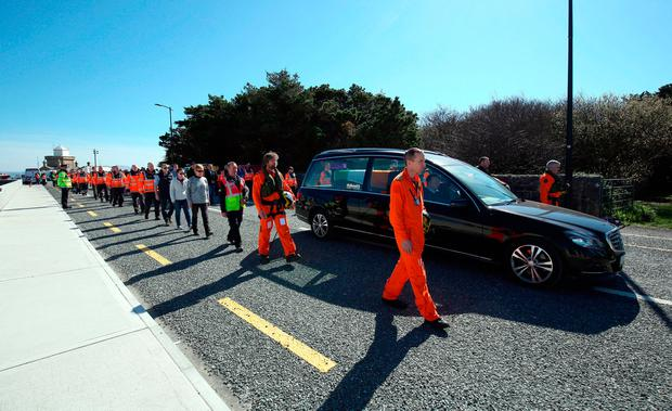 The hearse carrying Capt Mark Duffy to Mayo General Hospital is escorted by rescue workers. Photo: PA