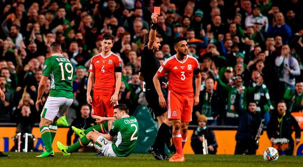 Referee Nicola Rizzoll shows Neil Taylor of Wales a straight red card during the FIFA World Cup Qualifier Group D match between Republic of Ireland and Wales at the Aviva Stadium in Dublin. Photo by Ramsey Cardy/Sportsfile