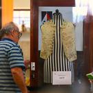 Potential buyers can be seen near the display case containing a 250-year-old embroidered silk waistcoat that belonged to Captain James Cook on a mannequin at Aalders Auctions house in Sydney, Australia, March 26, 2017. REUTERS/Steven Saphore