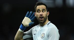 Manchester City's Chilean goalkeeper Claudio Bravo gestures to the Huddersfield fans after Manchester City's Nigerian striker Kelechi Iheanacho scored his team's fifth goal during the FA Cup fifth round replay football match between Manchester City and Huddersfield Town at the Etihad Stadium in Manchester, north west England, on March 1, 2017. AFP PHOTO / Oli SCARFF