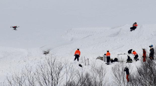 Firefighters and rescue workers using a drone investigate at the site of an avalanche in Nasu town, north of Tokyo, Japan, in this photo taken by Kyodo March 28, 2017. Photo: Kyodo/via REUTERS