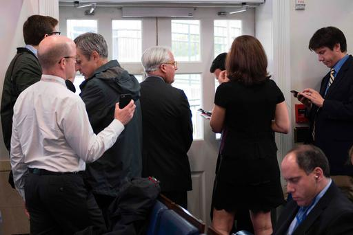 Members of the White House Press Corps stand behind the locked door of the briefing room at the White House in Washington during a lockdown for a suspicious package Photo: Getty Images