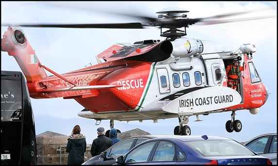 Family members or Rescue 116 missing crewmembers look on as an Irish Coast Guard Helicopter takes off at Blacksod Pier . Pic Steve Humphreys