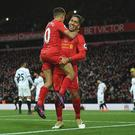 Liverpool's Brazilian midfielder Roberto Firmino (R) celebrates scoring his team's fourth goal with Liverpool's Brazilian midfielder Philippe Coutinho during the English Premier League football match between Liverpool and Watford at Anfield in Liverpool, north west England on November 6, 2016. / AFP / PAUL ELLIS / RESTRICTED TO EDITORIAL USE.