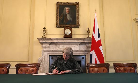British Prime Minister Theresa May signs the official letter to European Council President Donald Tusk invoking Article 50 Photo Reuters/Christopher Furlong/Pool
