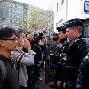 Demonstrators from the Asian community face riot police officers outside Paris's 19th district's police station yesterday. Three police officers were injured in protests and 35 protesters arrested, authorities said. Photo: Michel Euler/AP