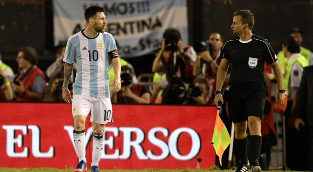 Lionel Messi (L) argues with first assistant referee Emerson Augusto de Carvalho during the half time of their 2018 FIFA World Cup qualifier against Chile. / AFP PHOTO / JUAN MABROMATAJUAN MABROMATA/AFP/Getty Images