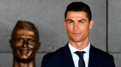 Portuguese footballer Cristiano Ronaldo stands next to a bizarre bust presented during a ceremony where Madeira's airport in Funchal is to be renamed after Cristiano Ronaldo, on Madeira island. / AFP PHOTO / FRANCISCO LEONGFRANCISCO LEONG/AFP/Getty Images
