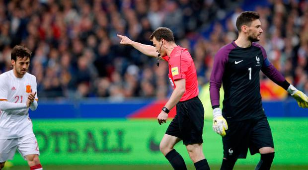 Spain's scorer David Silva, left, applauds as referee Felix Zwayer points to award a goal after consultation with a video referee during their win over France. Photo: AP