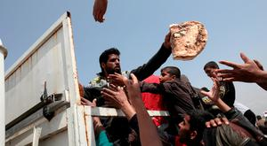 An Iraqi man delivers bread to displaced people outside of Hammam al-Alil camp in the south of Mosul. Photo: Reuters
