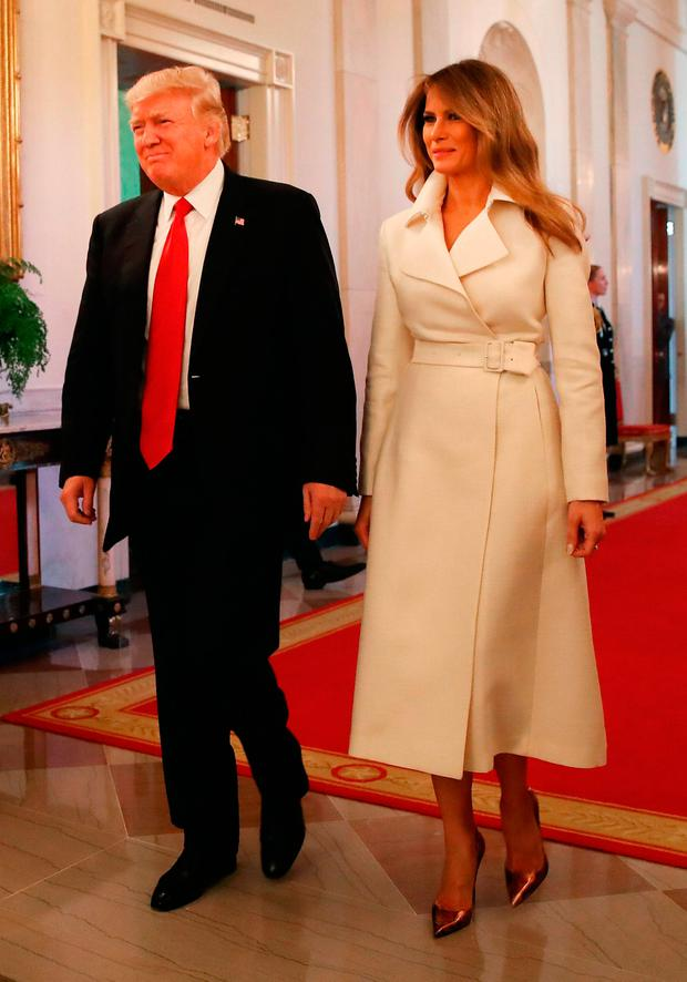 U.S. President Donald Trump and first lady Melania Trump walk into the East Room to attend an event celebrating Women's History Month, at the White House March 29, 2017 in Washington, DC. (Photo by Mark Wilson/Getty Images)